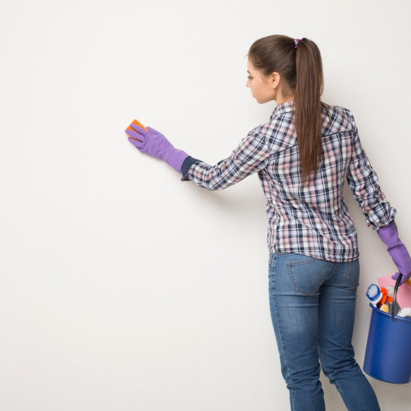 Girl cleans wall.